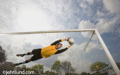 Picture of a Hispanic soccer goalie catching a soccer ball in mid air with the net filling the background behind him